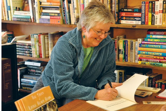 "Laura Tyler, of Craig, signs a copy of her book, ""The Story of Little Beaky Robin,"" on Saturday at Downtown Books & Beads. The first-time author chronicled her time with a young robin that fell out of his nest as Tyler nursed him back to health and cared for him until he learned how to fly."