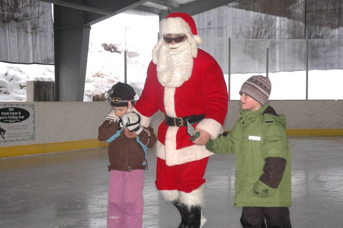 Eden Mayer, 5, left, and Gregory Rubalcaba, 7, skate Sunday with Santa Claus during an event at the Oak Creek Ice Rink.