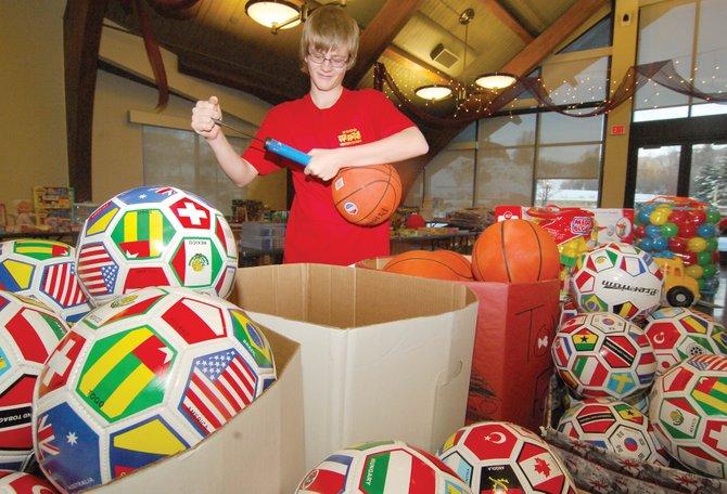 Matthew Dennis uses a hand pump to inflate a basketball Monday at Bud Werner Memorial Library, where local volunteers are collecting donations of unused, unwrapped gifts for local children and teenagers as part of a Toys for  Tots drive.  Volunteers will accept donations from 11 a.m. to 7 p.m. today and Wednesday.