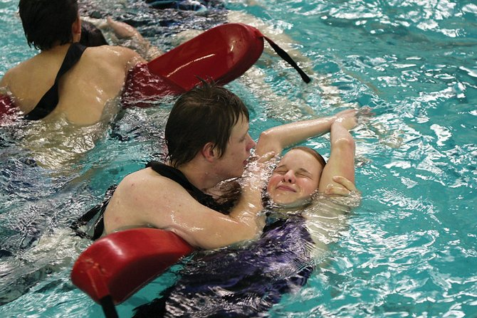 Chance Peterson, 17, left, practices a rescue technique with Tatiana Dulmaine, 15, during a lifeguard certification class at Moffat County High School. The class had 14 participants learning water rescue.
