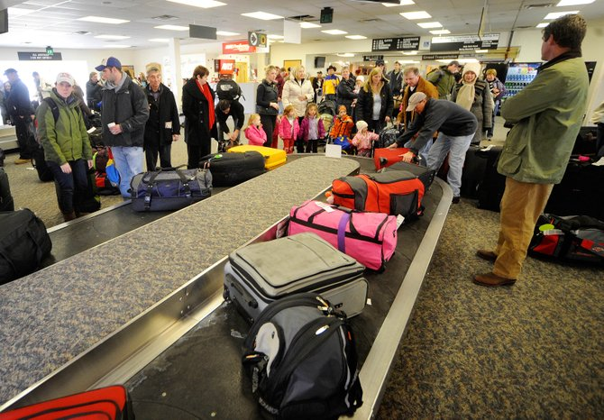 Air passengers pick up their bags Dec. 17 at Yampa Valley Regional Airport, where officials are takings steps to ensure things run smoothly during a busy holiday season.