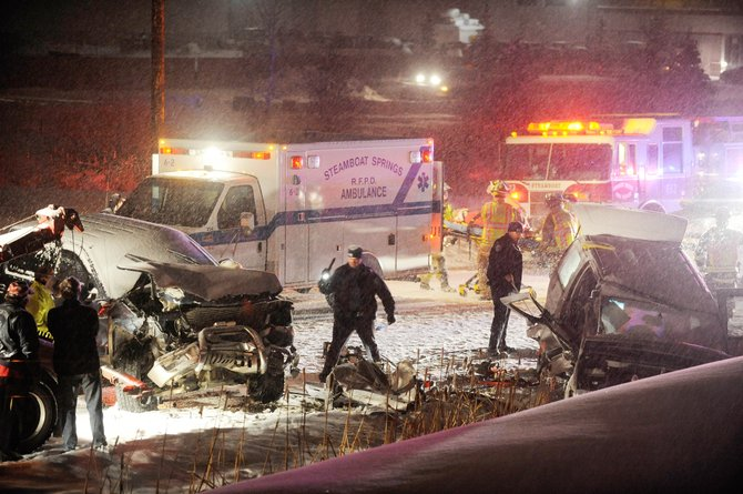 Police investigate a two-vehicle accident while Steamboat Springs Fire Rescue firefighters load a woman into an ambulance after extricating her from a vehicle Wednesday night on Elk River Road across from the Copper Ridge Business Park.