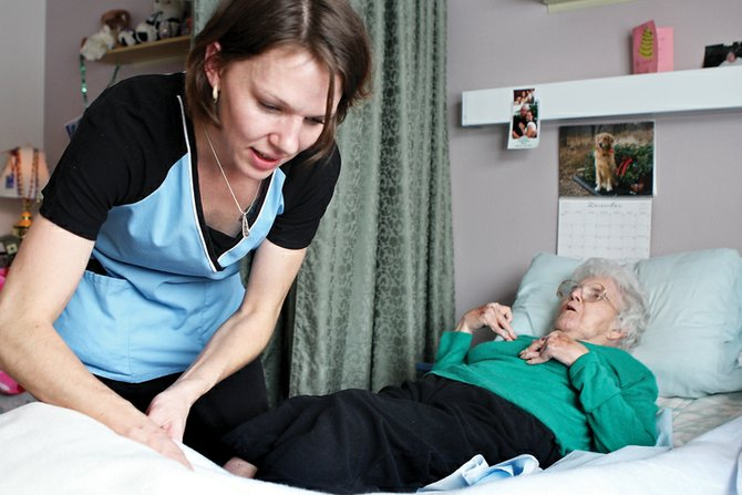 Kari Kalar, a certified nursing assistant, helps Helen Leabo, 79, get into her bed for a nap after lunch Thursday at Sandrock Ridge Care & Rehab. Kalar was named Employee of the Year for the facility.