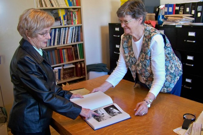 Doris Zimmerman, left, and Wilma Taylor-Baker look at a new oral history book of the Perry and Elizabeth Van Dorn family that recently was completed. Taylor-Baker was the interviewer for the oral history and Zimmerman is the daughter of Perry Van Dorn.