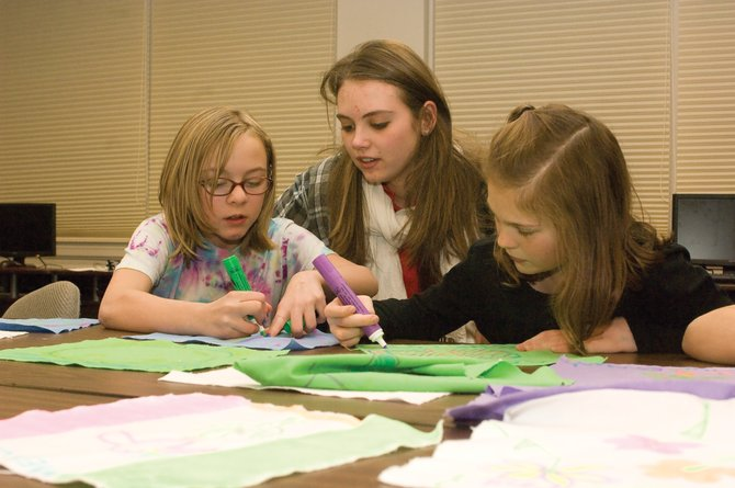 Laina Weinman, a junior staff member for the Boys & Girls Club of Steamboat Springs, helps Danielle Cooke, left, and Aubrie Moothart with squares for a quilt the group is making. The group is making two or three quilts, which will be delivered to an orphanage in Mexico as a gift.