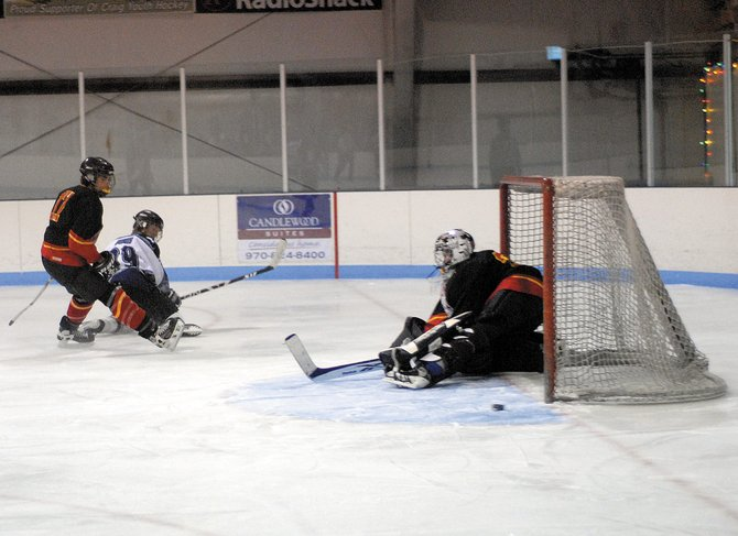 Moffat County's Cole DuBois, center, watches as a Crested Butte goalie deflects his shot in a Dec. 20 game in Craig. The Moffat County club hockey team is scheduled to resume play Sunday in Grand Junction.