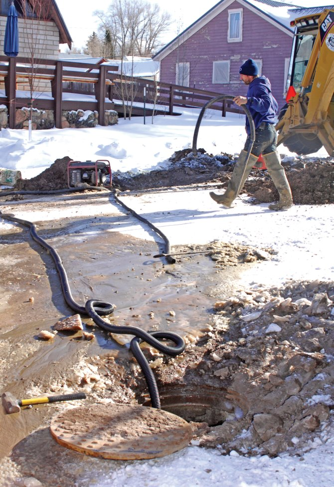 Oak Creek Public Works Department employee Rocky Wisecup works on an underdrain along South Sharp Street in Oak Creek on Monday. Water leaking from the pipe has flooded parts of the street and has left an icy mess in its wake.