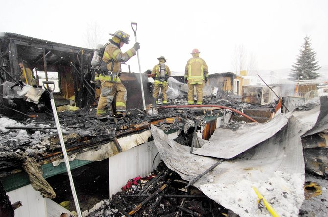 West Routt firefighters check for hot spots after a mobile home burned Tuesday in Hayden.