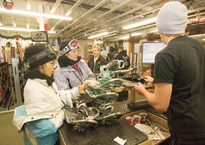 Ski Haus employee Greg Jansen helps, from left, Alexis Aquirre, Ann Ghent and Meg Ryan with snowshoeing gear Tuesday afternoon. The extended family members were visiting Steamboat Springs for a getaway from several areas of the country.