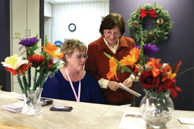 Deann Anderson, left, an administrative assistant at the Northwest Colorado Visiting Nurse Association, and Gisela Garrison, VNA Health Center director, look over paperwork Thursday at the VNA's Craig office. The VNA plans to expand its main floor to include more exam rooms to meet community needs.