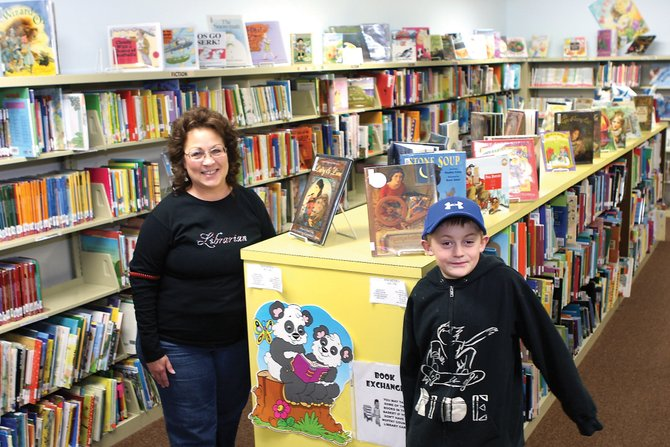 Charleah Firestone, left, a library assistant at the Craig branch of the Moffat County Libraries, poses with Graham Stecklein, 8, for a picture in the children's book room. Stecklein enjoys mystery books and R.L Stein is his favorite author. The library is offering a series of programs for Moffat County youths.