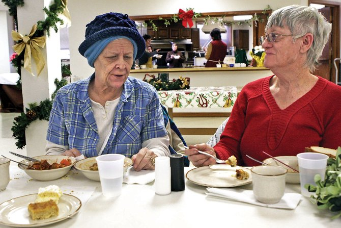 Elizabeth Beaulieu, left, and her friend Sylvia Queen enjoy a free lunch Tuesday at St. Michael Catholic Church. The free meal program will offer meals from noon to 2 p.m. Tuesdays and 4 to 6 p.m. Thursdays. The group urges members of the community to participate in the free meal by volunteering or showing up with an appetite.