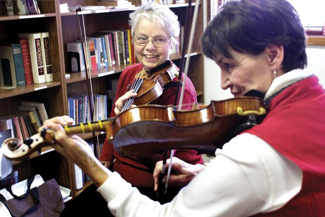 Sandra Kruczek, left, smiles at student Sally Smith during a violin lesson Thursday at St. Michael Catholic Church. Kruczek uses the Suzuki method of teaching, which reinforces hearing music and playing it by ear.