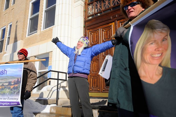 Routt County Commissioner Diane Mitsch Bush supporters Paul Reynolds, right, and Michael Turner, left, hold banners while Mitsch Bush announces her intentions to run for re-election Thursday at the Routt County Courthouse.