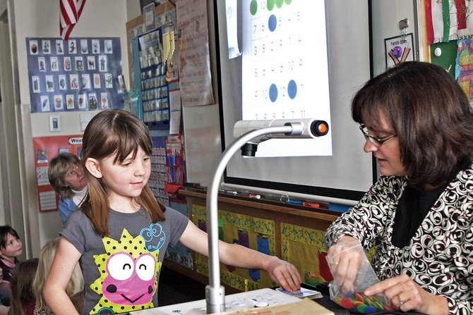 "Tressa Otis, 7, draws a card to play a game of bingo with her teacher, Karen Eitel, on the ELMO document camera being projected to other students during first-grade class at Ridgeview Elementary School. The game was called ""Plus One or Two Bingo,"" where a card with a number was pulled from the deck and the children had to decide to add one or two to make the best match for their bingo card."