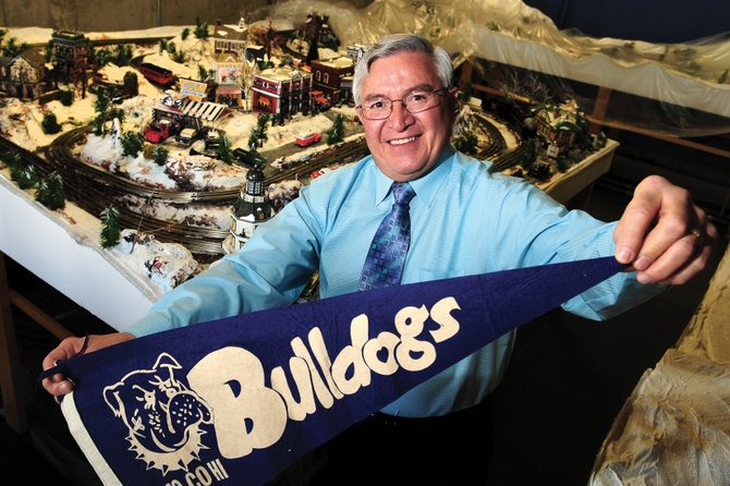 Cecil Gutierrez, of Loveland, shows his Bulldog spirit while standing in front of his handcrafted train set in the basement of his home Friday. Gutierrez, who is originally from Craig, was elected mayor of Loveland in November 2009 after two years as a city councilor.