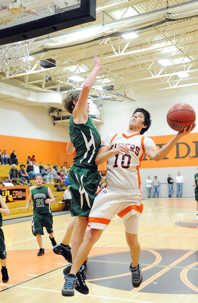 Hayden High School's Rene Valdez lofts a one-handed shot over Plateau Val­ley's Teddy Grundy on Saturday. The Tigers beat the Cowboys, 68-52