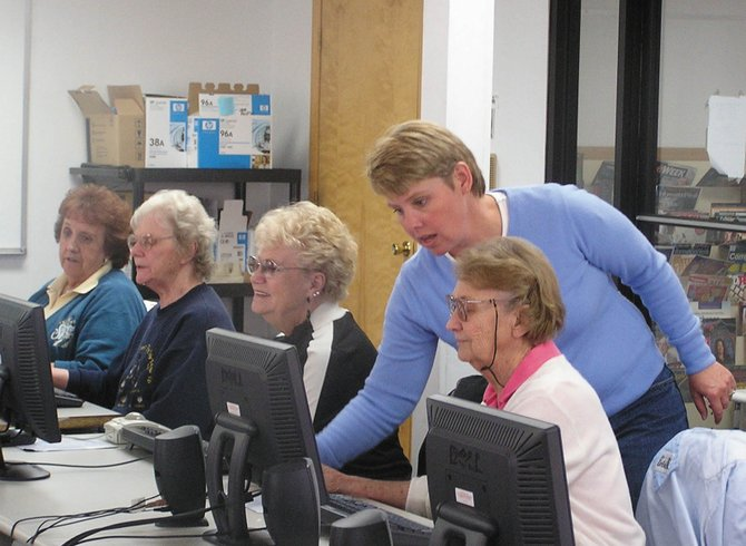 Melissa George helps students in the senior computer basics class at CNCC in Craig. The college is offering a similar class for older adults in Hayden during Wellness Days at The Haven Community Center.