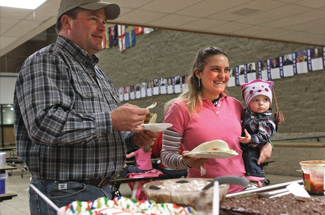 Jeff Clary fills his plate with his wife, Subrina, and their eighth-month-old daughter, Tyler, during a taco bar dinner and auction Tuesday night to benefit the Cystic Fibrosis Foundation at the Moffat County High School cafeteria. MCHS student council members, who sponsored the event, were auctioned off for three hours of snow removal to the highest bidders.