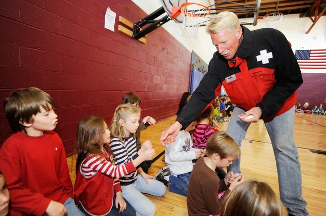 Steamboat Ski and Resort Corp. ski patroller Scott Halliday passes out temporary tattoos to South Routt Elementary School students after a presentation Wednesday about ski safety.