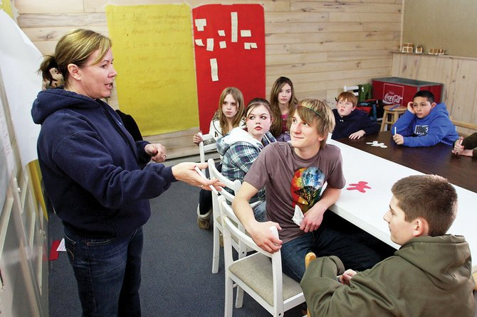Judy Harris, a sixth-grade language arts teacher at Craig Middle School, directs an exercise during a CMS leadership retreat Thursday in the back room of Serendipity Café & Coffee Shop. The students will be part of a new council that will give the CMS student body a voice.