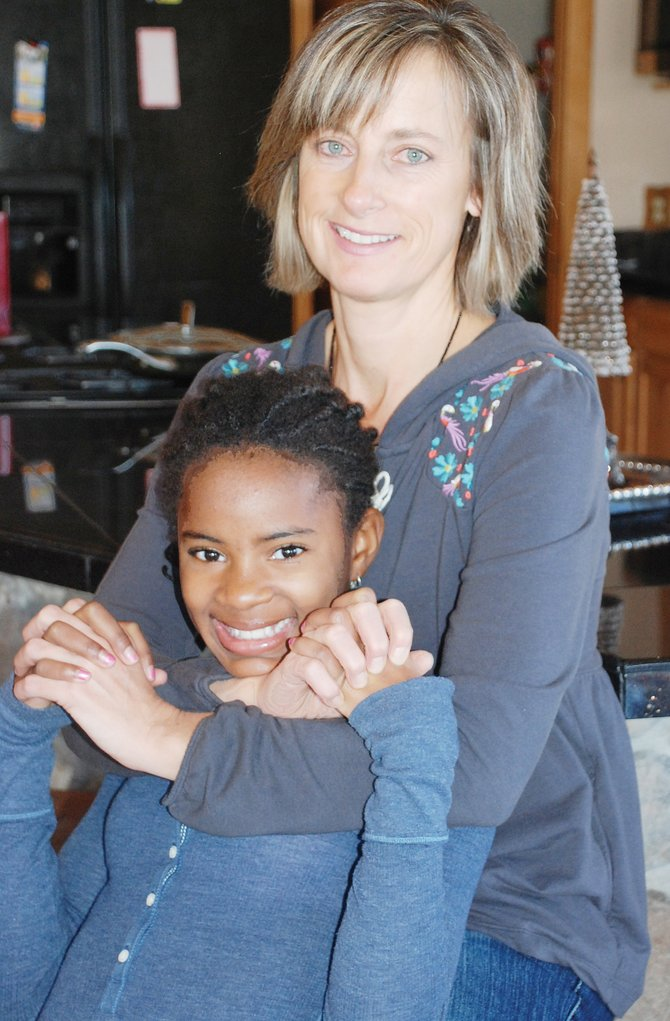 Tracy Metzler and her daughter Fena set aside their anxiety about the Haiti earthquake with a hug on Fena's 12th birthday Friday.