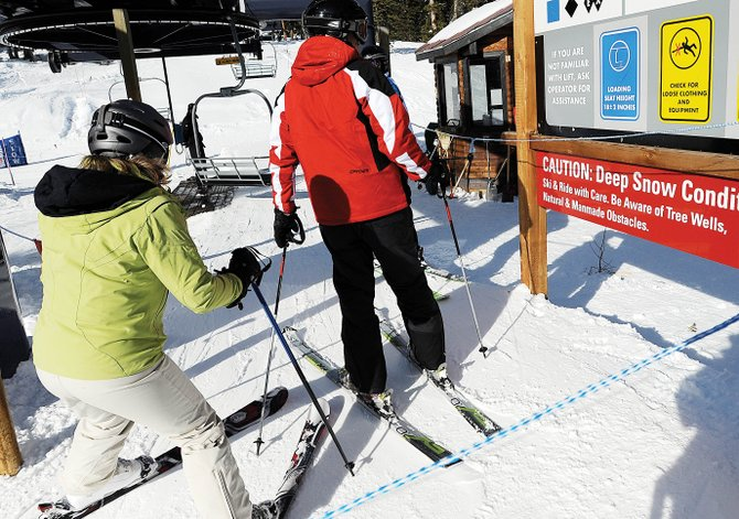 A pair of skiers line up next to a tree well warning sign as they wait to load the Morningside lift Wednesday afternoon at Steamboat Ski Area.