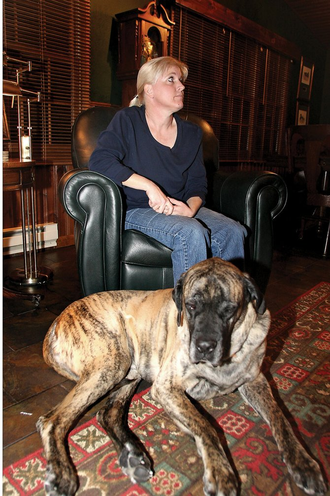 Kathy Osborn sits Saturday on a chair in her living room with Gunther, a 130-pound bull mastiff, at her feet. Kathy and her husband, Tim, have rescued many dogs like Gunther during their lives, including several with medical issues or a history of abuse.