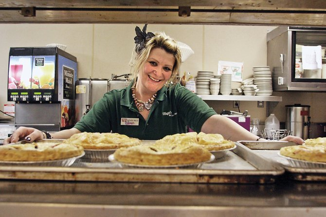 Natasha White smiles through the food service window Saturday night in the back of Village Inn. She has worked for the restaurant for nine years, and said she loves one aspect of her job above others — constantly being around people.