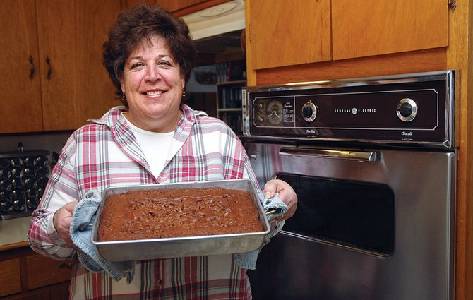 Joanne Roberson, a Craig resident and avid baker, stands with her chocolate chip zucchini cake Monday afternoon in her kitchen. Roberson, a past Taste of Chocolate winner, looks forward to competing in the event again next month.