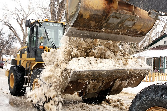 Moffat County Road Department workers clear ice and snow Thursday off School Street. Two front-end loaders worked together to move ice scraped from the street.