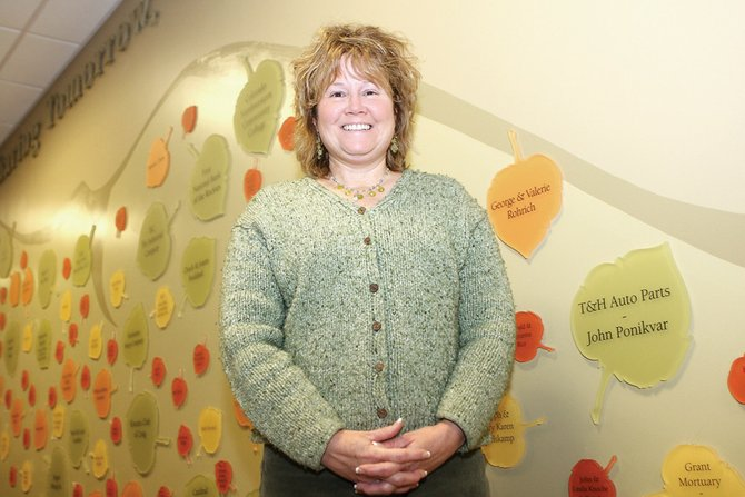Corrie Ponikvar stands in front of the donor wall Thursday at The Memorial Hospital. Ponikvar's five-year term on the hospital board is coming to an end.