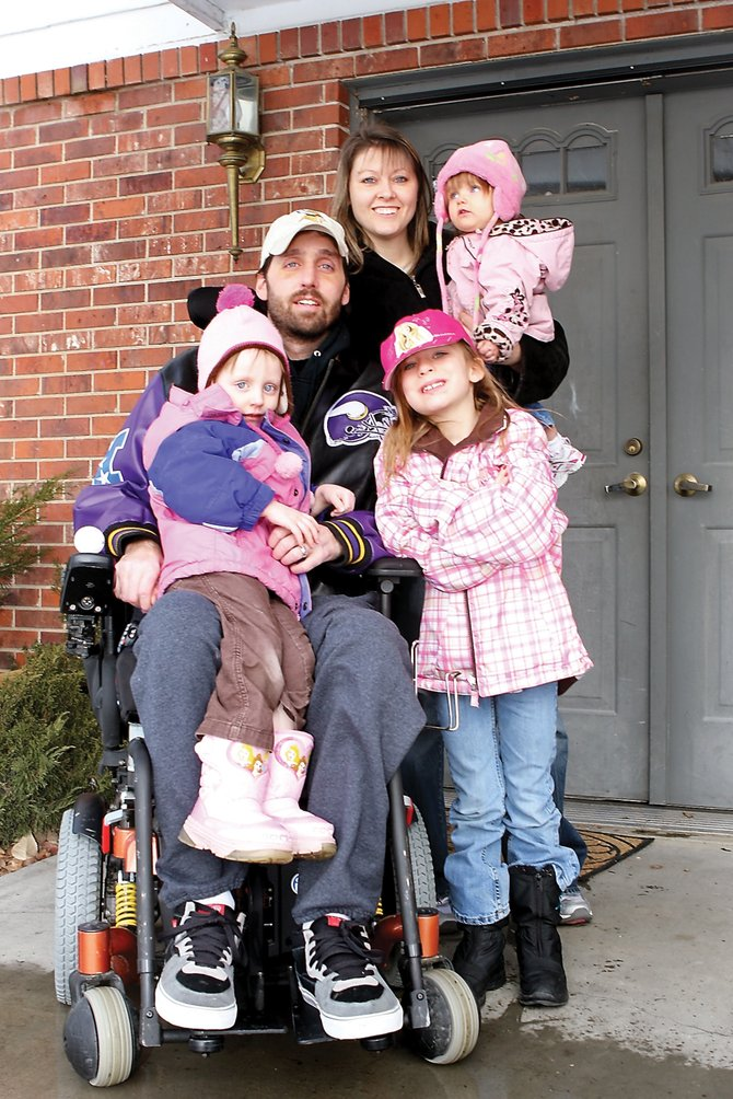 Rick Bustad holds his daughter, Brooklyn, 3, on his lap while his wife, Amy, cradles Lily, 1, with Annabella, 8, close by for a family portrait Friday in front of their Craig home. Rick is paralyzed from the chest down after a motorcycle accident May 11, 2009.