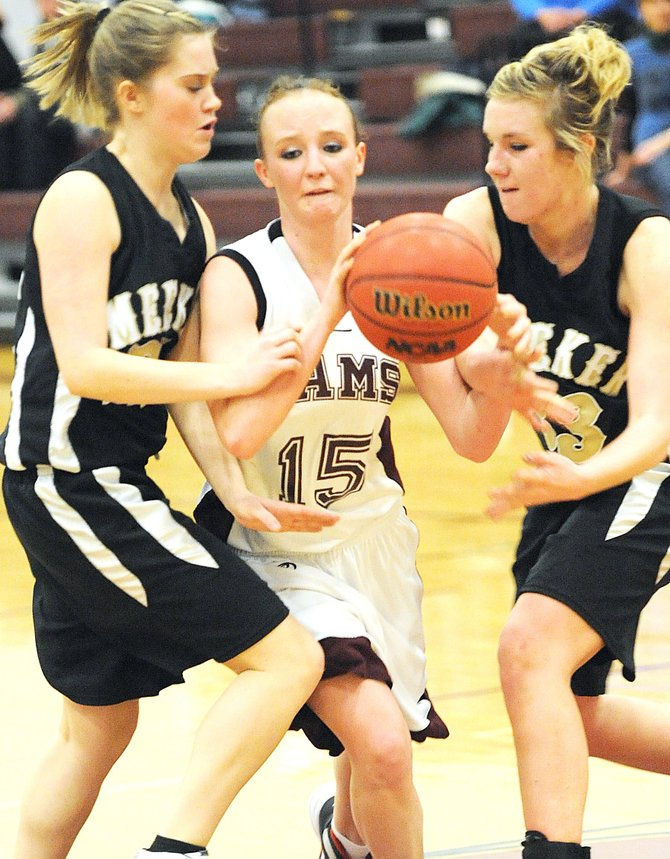 Soroco's Corey Snyder tries to thread her way through a pair of Meeker defenders Saturday night. The Rams lost to the Cowboys, 57-44.