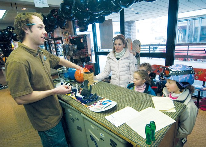 Jake Jarvis, manager at Powder Tools in Gondola Square, helps the Alter family with a snowboard rental Thursday morning. Amanda Alter listens as Jarvis explains the features of the board to her daughters Abby, middle, and Naomi, right. Their brother Adam is standing behind Abby. Ski industry leaders and retailers are finding the value of marketing gear and programs toward women and families.