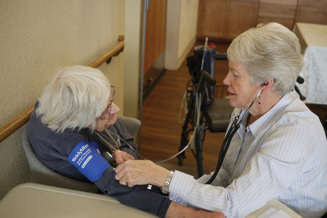 Registered nurse Joan Dalrymple, right, checks Alma Harris's blood pressure and pulse during a wellness clinic at The Haven Community Center. The free, drop-in clinics are held on a regular basis throughout Routt and Moffat counties.