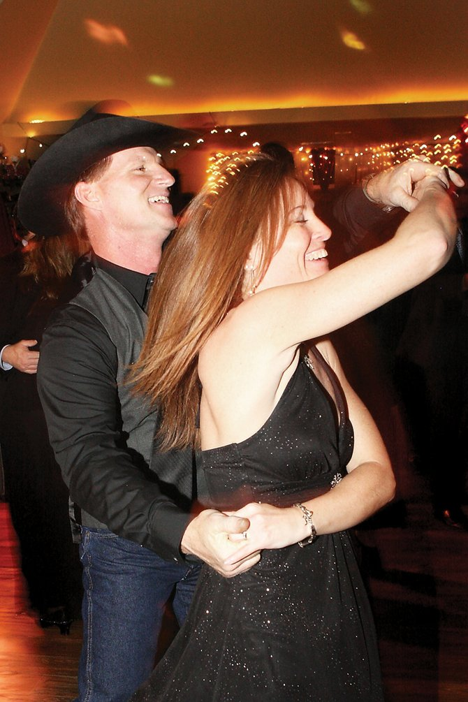 Mark Zimmerman spins his wife, Gayle, on the dance floor during the Rotary Club's Diamonds & Spurs event Saturday at the Moffat County Fairgrounds Pavilion. The event included cocktails, dinner, dessert and dancing with a disc jockey providing the music.