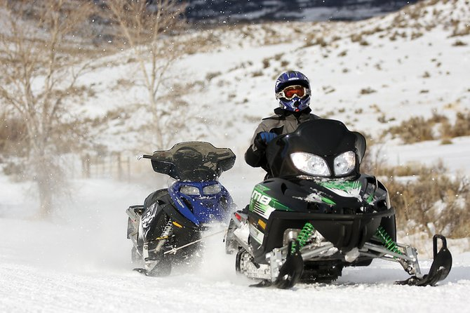 Kaleb Brown pulls a snow machine during the final leg of the Poker Run hosted by the Northwest Colorado Snowmobile Club on Saturday at the Freeman Reservoir trailhead. The snowmobile in tow, which Brown's father was riding in the event, blew its clutch.