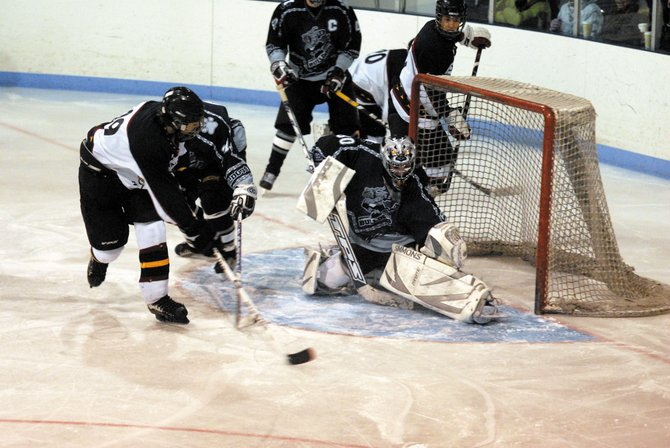 Moffat County goalie Curt Ellgen deflects a Gunnison shot in the first period of Sunday's game. Ellgen stopped 21 of 23 shots on net as the Bulldogs won, 3-2.