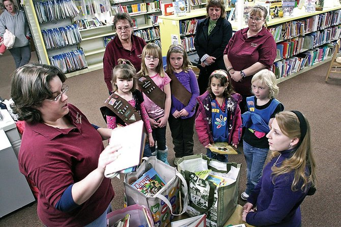 Jolene Keith, left, shows off a few of the children's books collected by local Girl Scout troops. Several Girl Scouts and leaders gathered Thursday at the Craig branch of the Moffat County Libraries to donate 75 new children's books as part of a community service project.