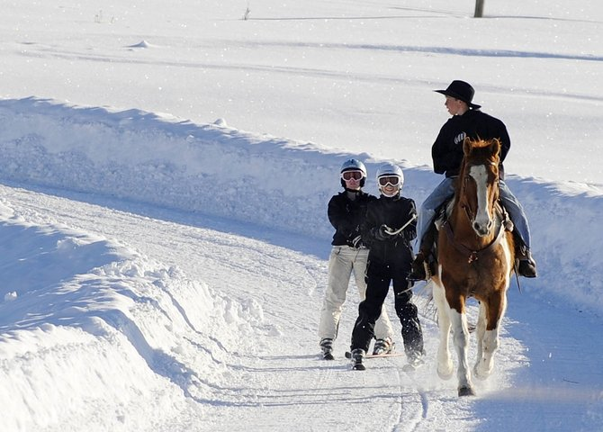 North Routt Community Charter School student Will Zupan rides his horse, Bubba, to pull Mary White, left, and his sister Zava down the driveway Friday to practice skijoring in preparation for this week's Winter Carnival.