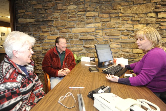 Steamboat Springs Wells Fargo personal banker Shauna Cagnoni helps Ron and Dianne Revell open an account Friday afternoon.