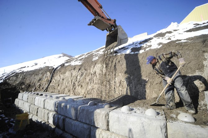 Duckels Construction worker Juan Cortes works on a retaining wall along the New Victory Highway road off Downhill Drive on Thursday. The road could someday serve the Steamboat 700 development.