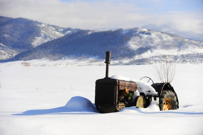 An old John Deere tractor no longer in service sits in a snow-covered hay meadow at the Brown Farms along Colorado Highway 131 just south of Steamboat Springs.
