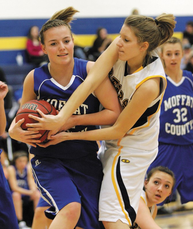 Moffat County's Annie Sadvar, left, fights for a loose ball Saturday against Rifle. The league-leading Bears were able to outlast the Bulldogs, 56-45.