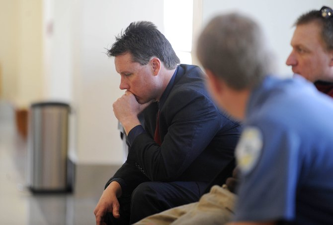 Steamboat Springs Police Department Detective Nick Bosick, left, waits with Detective Jerry Stabile, right, and Capt. Joel Rae outside a Routt County Justice Center courtroom Tuesday to testify in the Capote trial.