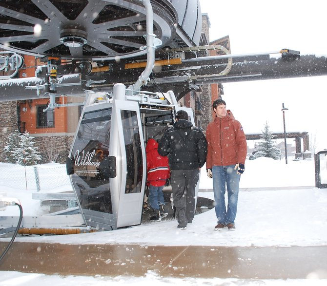 Resort Ventures West Director of Sales and Marketing Kerry Shea, right, helps guests board the new Wildhorse Meadows gondola outside Trailhead Lodge on Monday.