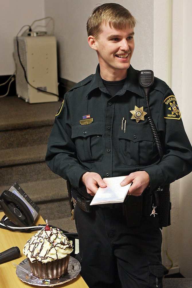 Jarrod Poley, a Moffat County Sheriff's Office deputy, smiles after being given an enormous cupcake Wednesday for his heroism in saving a choking baby a day earlier at the Moffat County Courthouse. The cupcake was a gift from courthouse co-workers.