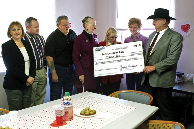 Jim Isgar, far right, state director of the United States Department of Agriculture Rural Development, hands over a check from his department for $460,000 to the Independent Life Center on Wednesday at the ILC office on Yampa Avenue. Also pictured, from left, are Pattie Snidow, northwest director of USDA Rural Development; P.J. Howe, area specialist for USDA Rural Development; Bud Nelson, ILC board vice president; Evelyn Tileston, ILC executive director; Sharon Stoddard, ILC president; and Sandra Gardner, ILC board member.