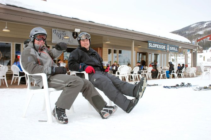 Trabis Greenlee, left, and Dan Ohnsman relax while watching skiers go by the seating area in front of the Slopeside Grill at the base of Steamboat Ski Area on Wednesday after a day on the slopes.